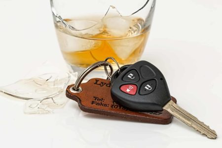 glass of alcohol next to keys - drunk driving article