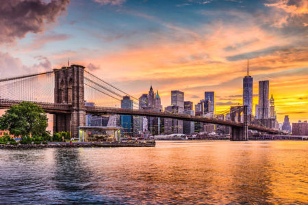 New York City, New York skyline on the East River with Brooklyn Bridge at sunset.